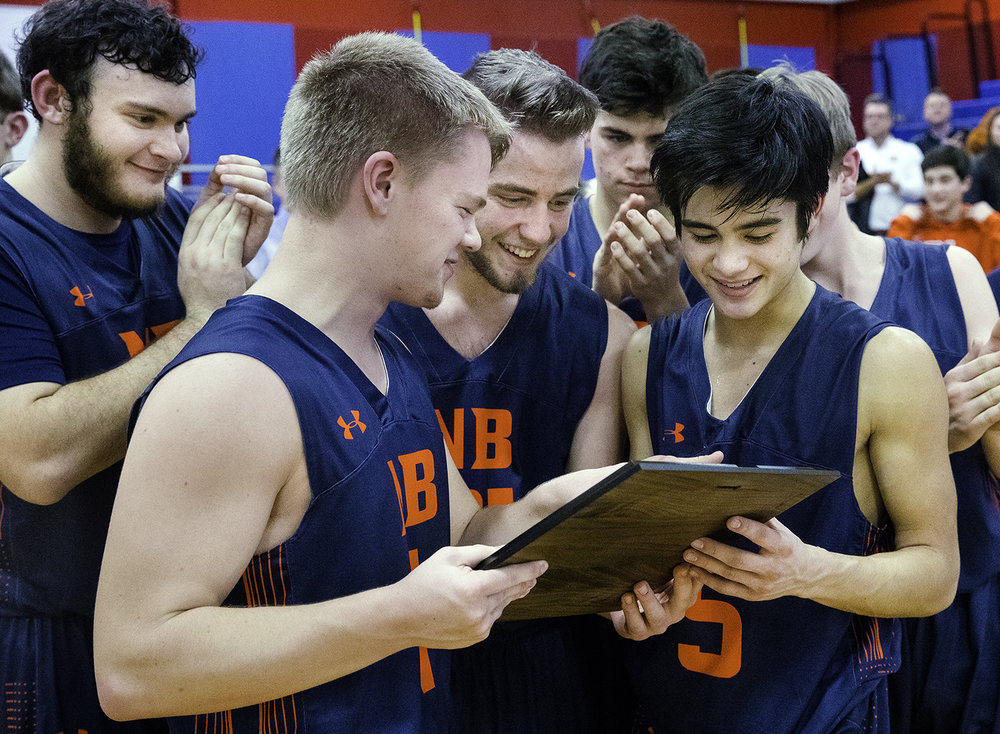 New Berlin's Dalton Minder, left, Luke Emmert and Christian Knox examine the championship plaque after defeating Williamsville during the championship game of the Sangamon County Tournament Friday at Lincoln Land Community College, Jan. 12, 2018. The three noted the date of the last time the Pretzels won the title, 1966. [Ted Schurter/The State Journal-Register]