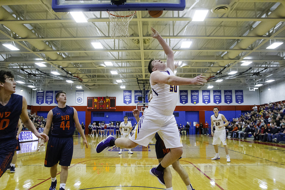 Williamsville's Hayden Moore flips in a reverse shot against New Berlin during the championship game of the Sangamon County Tournament Friday at Lincoln Land Community College, Jan. 12, 2018. [Ted Schurter/The State Journal-Register]