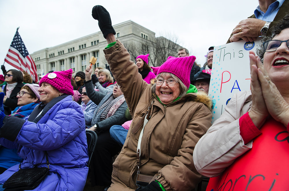 Liliana Costa, center, an immigrant from Costa Rica who arrived in 1956 and now lives in Jacksonville, Ill., expresses her support during the Action Illinois Springfield 'Women's March to the Polls' rally and march Saturday, Jan. 20, 2018. [Ted Schurter/The State Journal-Register]