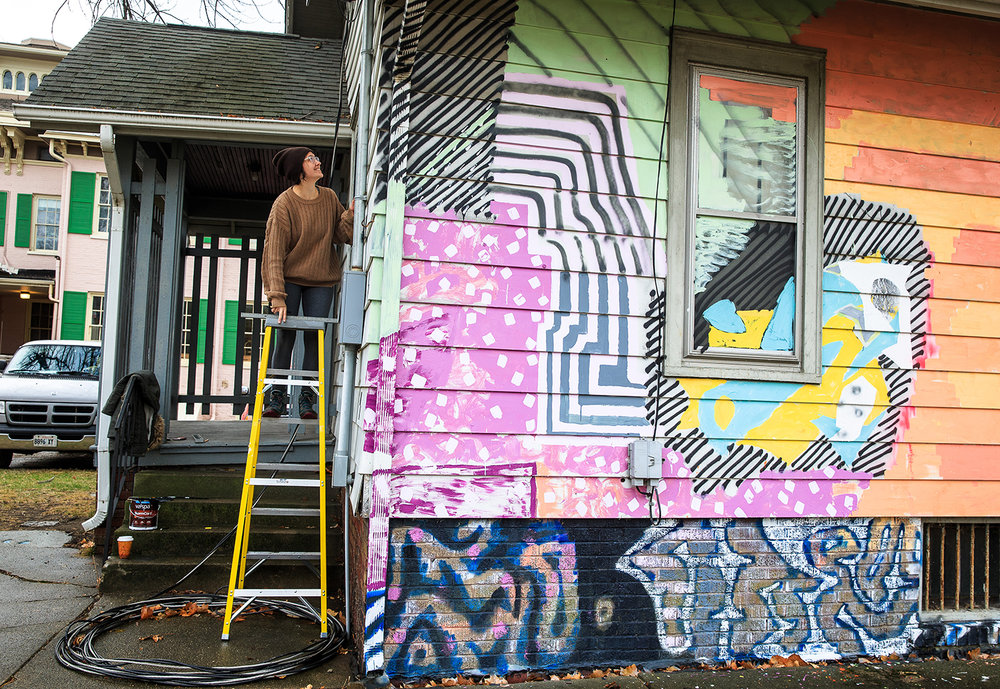 "Grace Katalinich, center, a junior member of the DEMO Project, scales a ladder to draw in the installation of a piece by Tom Burtonwood that includes 3D scanning targets on the rear facade of the The DEMO Project facility, a space donated for use by the Springfield Art Association and directed by artists affiliated with the University of Illinois Springfield, at 732 N. 4th St., Thursday, Jan. 11, 2018, in Springfield, Ill. Burtonwood did 3D scans of the house and used them to create a 3D print for a piece called ""Offset Registration"" that was an exhibit in the house. The farewell party for the house will be on Saturday Jan. 13th from 2-5 p.m. [Justin L. Fowler/The State Journal-Register]"