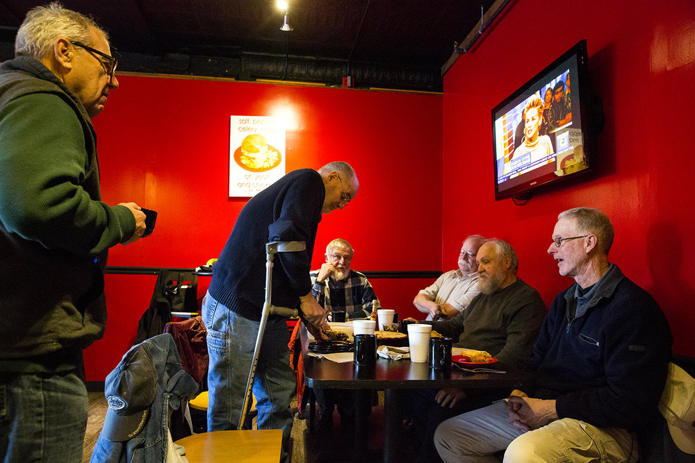 David Brady cuts into a walnut raisin pie he made to share with a group of friends who gather every week for breakfast at Cafe Moxo Thursday, Jan. 18, 2018 in Springfield, Ill. The informal gatherings were started 20 years ago by John Paul, owner of Prairie Archives Antiquarian Booksellers, and Brady, a former employee. From left are Tom Hiler, Brady, Doug Carr, Jim Allen, Paul and Steve Foss. [Rich Saal/The State Journal-Register]