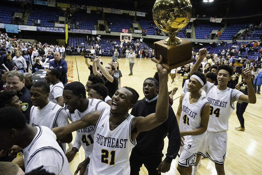 Southeast's Anthony Fairlee brings the championship trophy to the Southeast fans after the Spartans defeated Lanphier during the Boys City Tournament championship at the Bank of Springfield Center Saturday, Jan. 20, 2018. [Ted Schurter/The State Journal-Register]