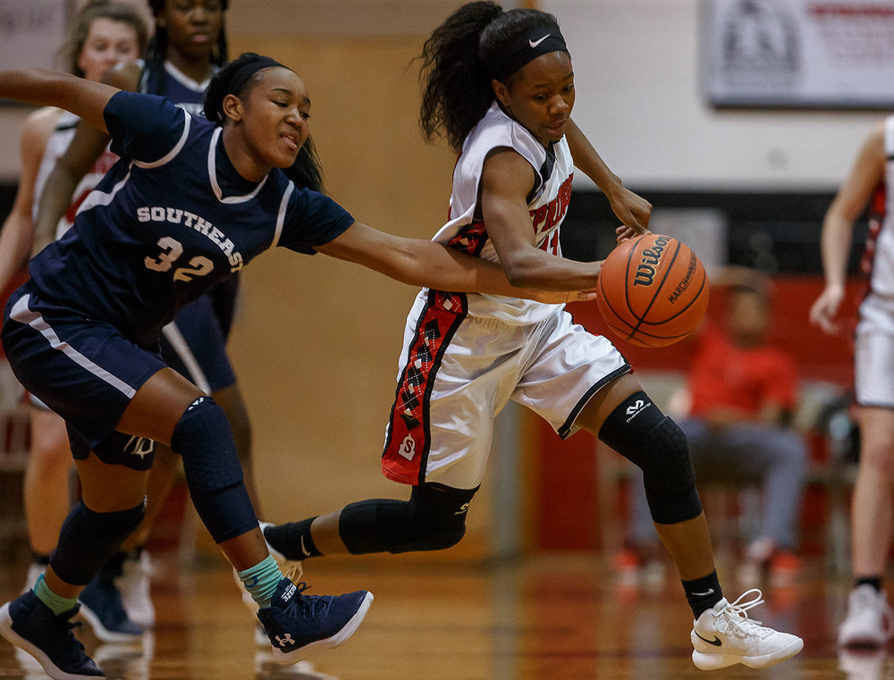 Springfield's Ozzy Erewele (11) steals the ball away from Southeast's Jadelyn King (32) in the first half on the opening night of the Girls City Tournament at Springfield High School, Wednesday, Jan. 24, 2018, in Springfield, Ill. [Justin L. Fowler/The State Journal-Register]