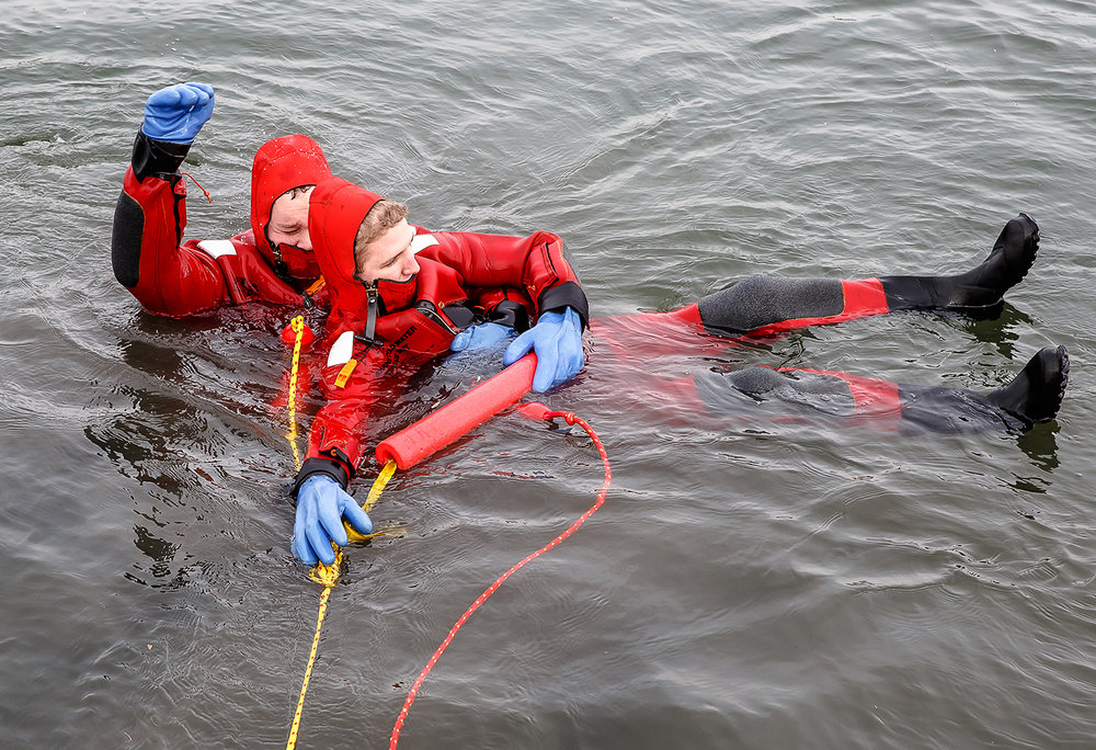 "Springfield firefighter Jeff Heubner raises his hand to signal firefighters on shore to pull them back in as he performs a mock rescue of firefighter Josh Banks while wearing cold water rescue suits during training at the pond at Knights Action Park, Wednesday, Jan. 31, 2018, in Springfield, Ill. Every firefighter in the department goes through the annual ice training that gives them invaluable experience in rescue techniques while using the cold water rescue suits. The training is normally done on ice, but the training was still done in the 35 to 40 degree water giving firefighters experience performing rescue operations in the suits. ""Every rig in town has somewhere in their running district a location that has water, that could potentially need a rescue,"" said Capt. Ryan Sabo with the Springfield Fire Dept. [Justin L. Fowler/The State Journal-Register]"