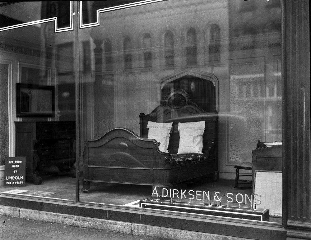 """Window display at A. Dirksen & Son furniture store showing bed reportedly used by Abraham Lincoln, October 22, 1937. File/The State Journal-Registerfurniture; downtown; retail; history; Lincoln; archive; spihistoryPublished as Picturing the Past, Feb. 11, 2018.A sign in the window of the A. Dirksen & Sons furniture store at Fourth and Washington streets implied that Abraham Lincoln slept in this bed. And ate meals at the table. And hung his hat on the hat rack. The truth, however, is not as clear as the view from the sidewalk. In October 1937, the city was celebrating the centennial of becoming the state capital, and it was in that spirit that Dirksen presented several household furnishings from the home of William Butler, a friend of Lincoln's in the years after he moved to town from New Salem. The furniture, loaned to the store by Butler's grandson, William J. Butler, was reported to be in the elder Butler's house during that period, presumably accumulating a little wear and tear thanks to the future president. James Cornelius, Curator of the Lincoln Collection at the Abraham Lincoln Presidential Library & Museum, points out that before marrying Mary Todd in 1842, Lincoln lived with Josuha Speed and William Herndon for most of 1837 to early 1841. He may have boarded at the Butlers, Cornelius says, meaning he may have taken some meals there and visited from time to time, but it isn't possible that Lincoln ever used the bed. It's design doesn't fit the time period. Susan Hakke, Curator at the Lincoln Home National Historic Site, agrees, and dates the bed from 1870-1880. """"Furniture with that heavy massing wasn't manufactured until after the Civil War,"""" she says.The story proves how tricky it can be to trace the provenance of a historical piece. """"Family stories are a hard thing to destroy as they get passed down for so many generations to so many people,"""" Hakke says. Cornelius adds, """"Sources can be misinformed in all eras, we have found. We try to, and tend to, believ"""