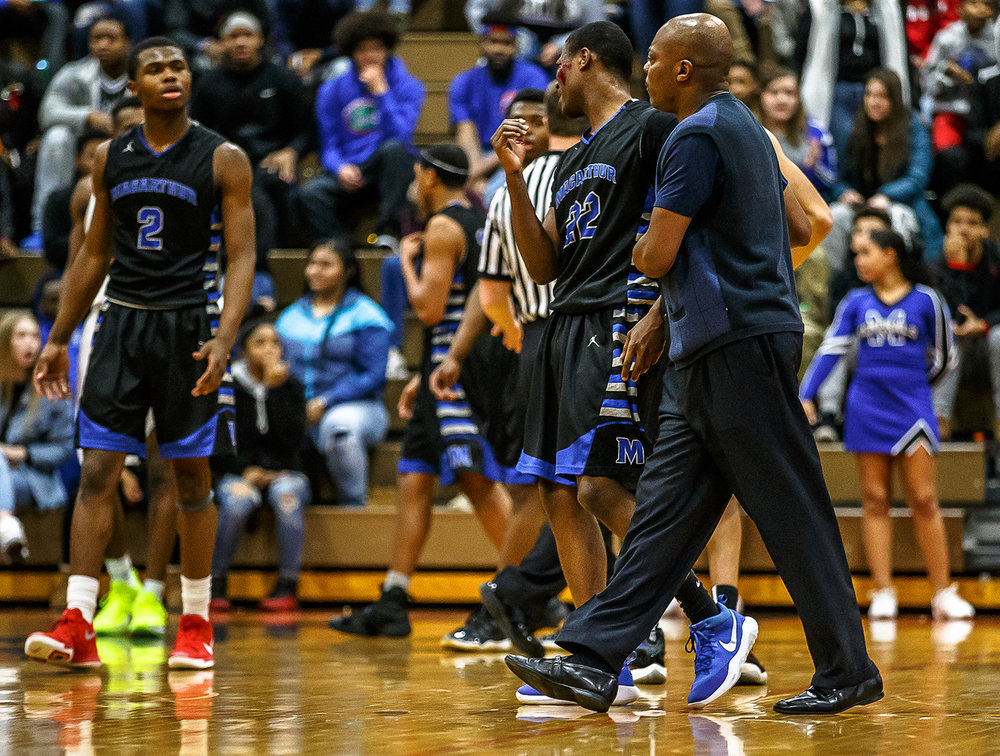 Decatur MacArthur boys basketball head coach Ron Ingram walks Decatur MacArthur's Keenan Ingram (22) off the court as blood runs down his face after taking a hard foul from Lanphier in the second half at Lober-Nika gymnasium, Saturday, Feb. 10, 2018, in Springfield, Ill. [Justin L. Fowler/The State Journal-Register]