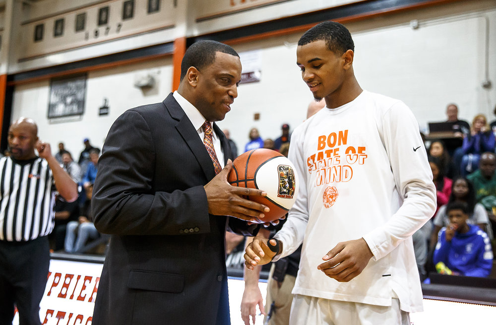 Lanphier boys basketball head coach Blake Turner honors Lanphier's Cardell McGee (12) with a commemorative ball after McGee crossed the the 1000 point mark in his career at Lober-Nika gymnasium, Saturday, Feb. 10, 2018, in Springfield, Ill. [Justin L. Fowler/The State Journal-Register]