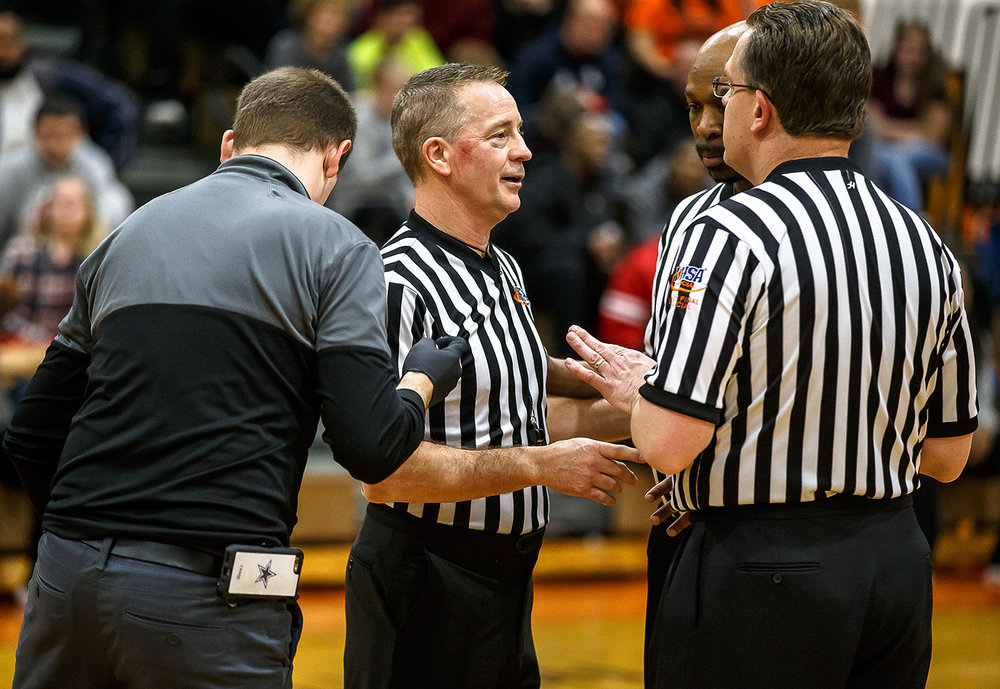 Referee Rod Peavler, of Rantoul, Ill., has a cut attended to by the trainer after breaking up a fight between Lanphier and Decatur MacArthur in the second half at Lober-Nika gymnasium, Saturday, Feb. 10, 2018, in Springfield, Ill. [Justin L. Fowler/The State Journal-Register]