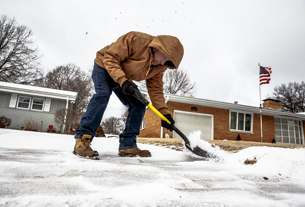 "Fred Selby navigates the icy incline of a driveway as he tries to clear it from ice for a customer on Lincoln Avenue after overnight rounds of snow, sleet and freezing rain, Sunday, Feb. 11, 2018, in Springfield, Ill. ""Oh man this is a workout, this is like scooping asphalt,"" said Selby, who clears driveways as a side job, of trying to clear the tough layer of ice. ""Like going to the gym in cold weather.""  [Justin L. Fowler/The State Journal-Register]"