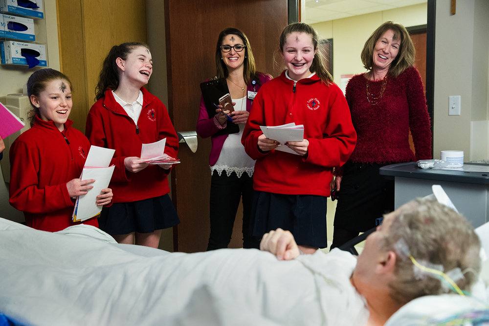 Little Flower School sixth grade students, from left, Libby Kulek, Lilly Drea and Ella Harrison, joined by Catie Sheehan, Executive Director of Communications, Marketing & Advocacy HSHS Central Illinois Division Hospitals, and teacher Tracy McDermott, deliver hand-made Valentine's Day cards to patient Fred Blevins at HSHS St. John's Hospital Wednesday, Feb. 14, 2018. Students in grades three through eight made more than 200 cards that were distributed to patients to mark the holiday. [Ted Schurter/The State Journal-Register]