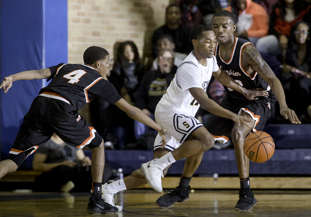 Southeast's Kobe Medley drives past Lanphier's Larry Hemingway and Lanphier's Karl Wright  at Southeast High School Tuesday,  Feb. 20, 2018. [Ted Schurter/The State Journal-Register]