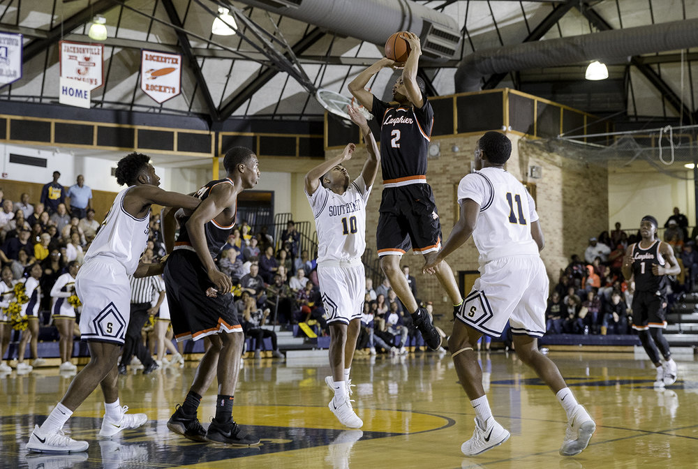 Lanphier's Cardell McGee fires a shot in front of Southeast's Damon Davis at Southeast High School Tuesday,  Feb. 20, 2018. [Ted Schurter/The State Journal-Register]