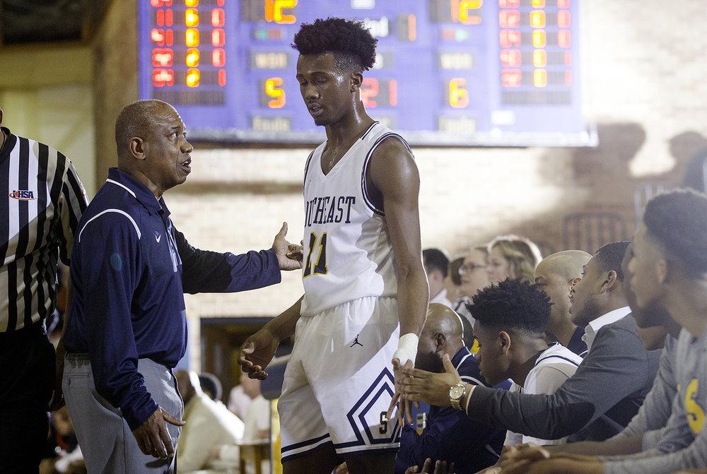 Southeast head coach Lawrence Thomas talks with Southeast's Anthony Fairlee after he picked up his second foul against Lanphier at Southeast High School Tuesday,  Feb. 20, 2018. [Ted Schurter/The State Journal-Register]