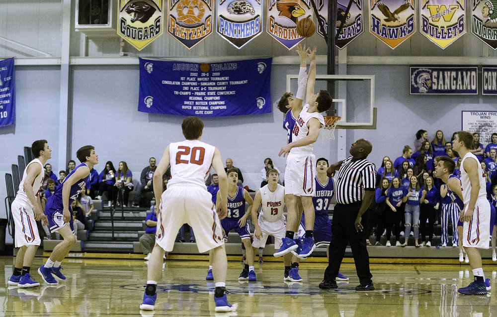 Auburn's Benji Eaker and Pleasant Plains' Joel Niermann leap for the opening tip during the Class 2A Auburn Regional at Auburn High School Wednesday,  Feb. 21, 2018. [Ted Schurter/The State Journal-Register]