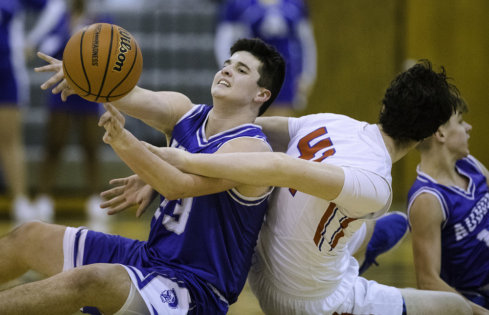 Auburn's Justin Tanner passes the ball from the floor as Pleasant Plains' Chase Schmitt tries to deflect the pass while reaching behind him during the Class 2A Auburn Regional at Auburn High School Wednesday,  Feb. 21, 2018. [Ted Schurter/The State Journal-Register]