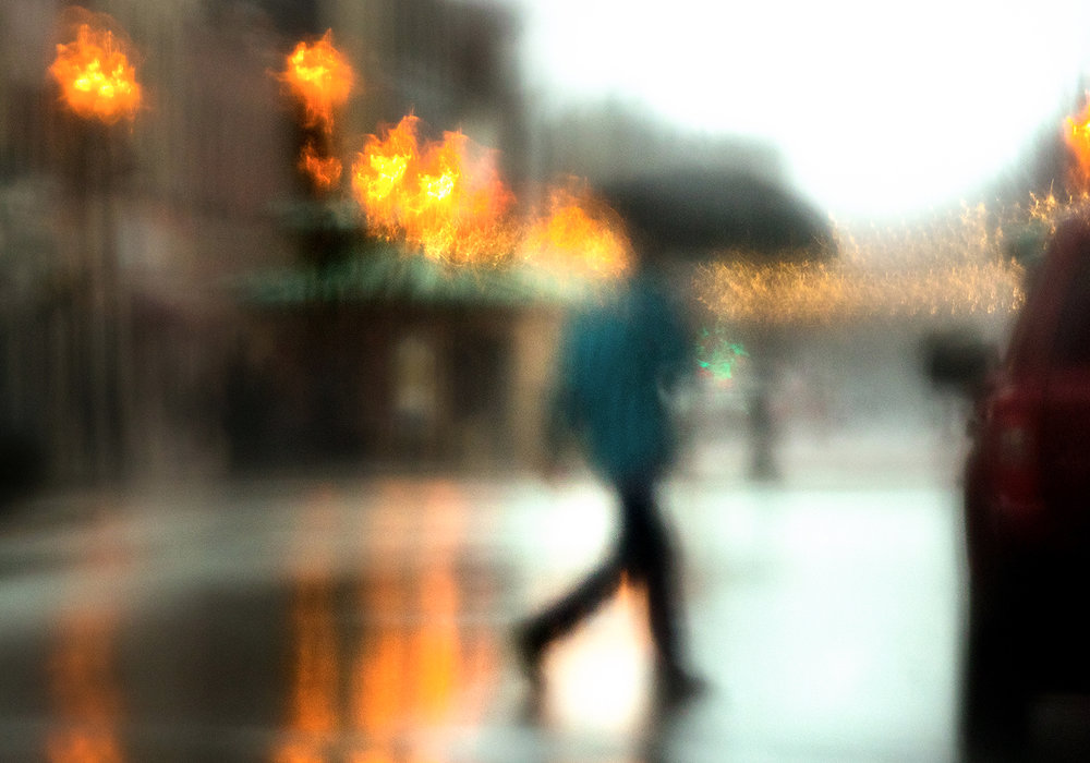 Viewed through a rain-smeared window, the intersection of Sixth Street and Adams Street takes on an impressionistic tone as an umbrella-toting pedestrian crosses to the other side during persistent rain Tuesday, Feb. 20, 2018. [Ted Schurter/The State Journal-Register]