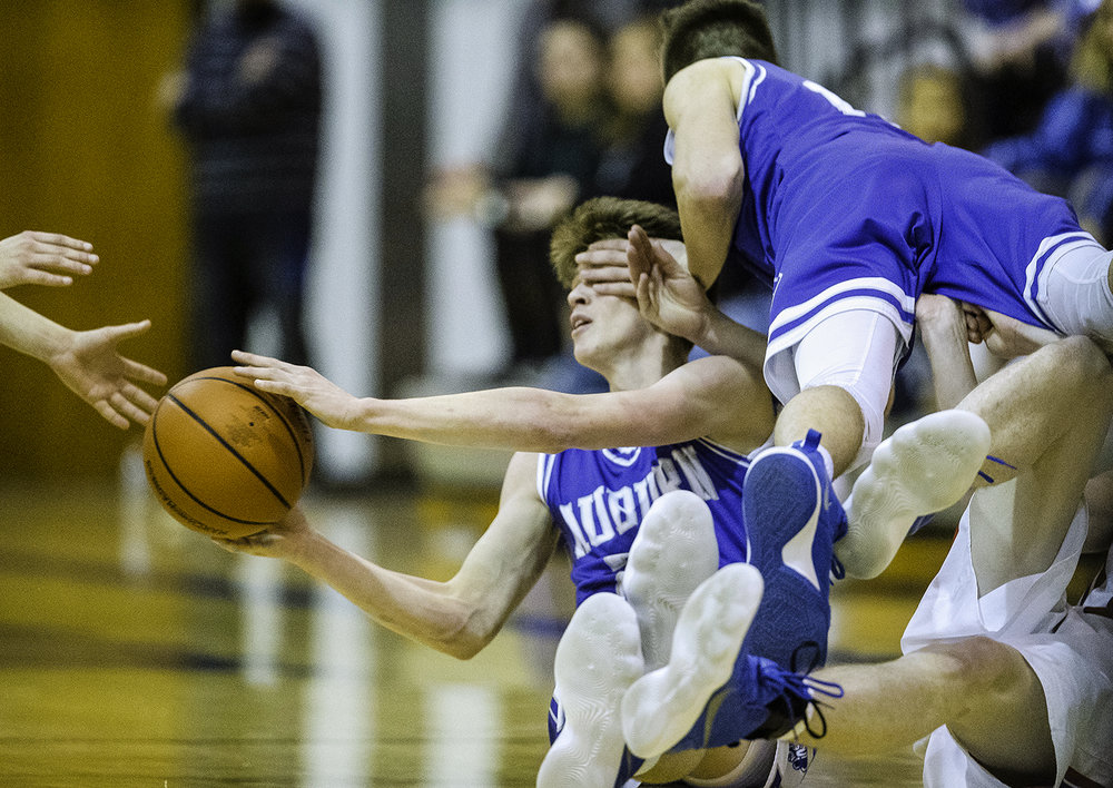 Auburn's Destin Chance hands the ball off as he is knocked to the ground by a teammate during the Class 2A Auburn Regional at Auburn High School Wednesday,  Feb. 21, 2018. [Ted Schurter/The State Journal-Register]