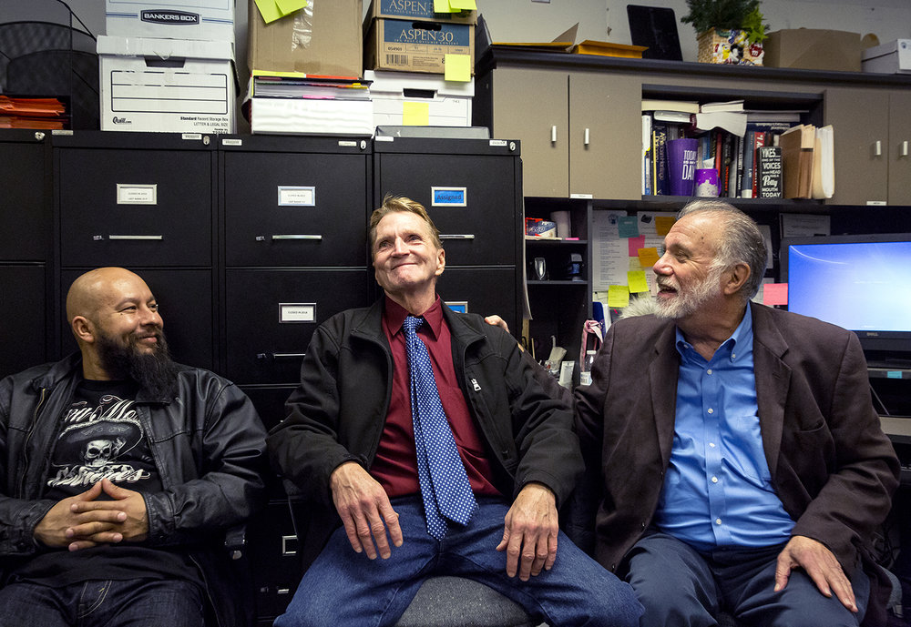 Bill Amor, center, who spent 22 years in prison for a crime he did not commit, visits with Larry Golden, right, director of the University of Illinois Springfield-based Illinois Innocence Project Friday, Feb. 23, 2018 in their office on the UIS campus in Springfield, Ill. Amor was acquitted Thursday by a DuPage County judge during a retrial of his 1995 arson murder case. He traveled to Springfield to thank the staff and volunteers at the project for their help on his behalf. At left is Angel Gonzalez, who the project helped exonerate in 2015. [Rich Saal/The State Journal-Register]
