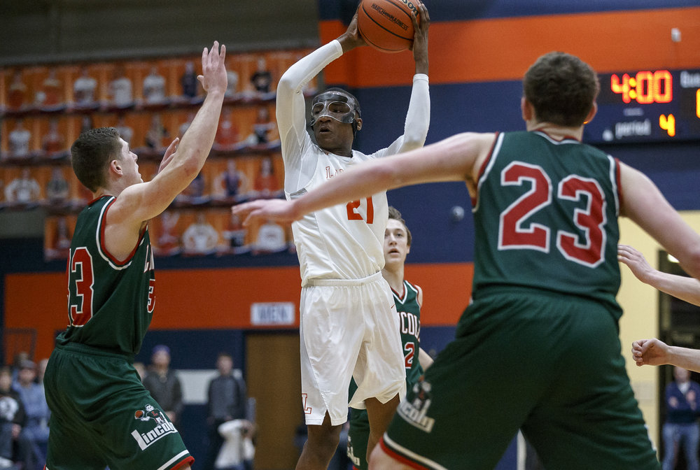 Lanphier's James Jones (21) passes the ball away while being pressured by Lincoln's Isaiah Bowers (33) in the second half of the Class 3A Rochester Regional title game at the Rochester Athletic Complex, Friday, March 2, 2018, in Rochester, Ill. [Justin L. Fowler/The State Journal-Register]
