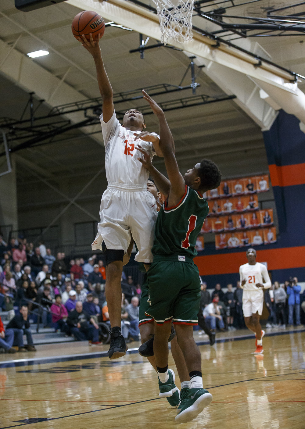 Lanphier's Cardell McGee (12) goes up for a basket against Lincoln's Titus Cannon (1) in the second half of the Class 3A Rochester Regional title game at the Rochester Athletic Complex, Friday, March 2, 2018, in Rochester, Ill. [Justin L. Fowler/The State Journal-Register]