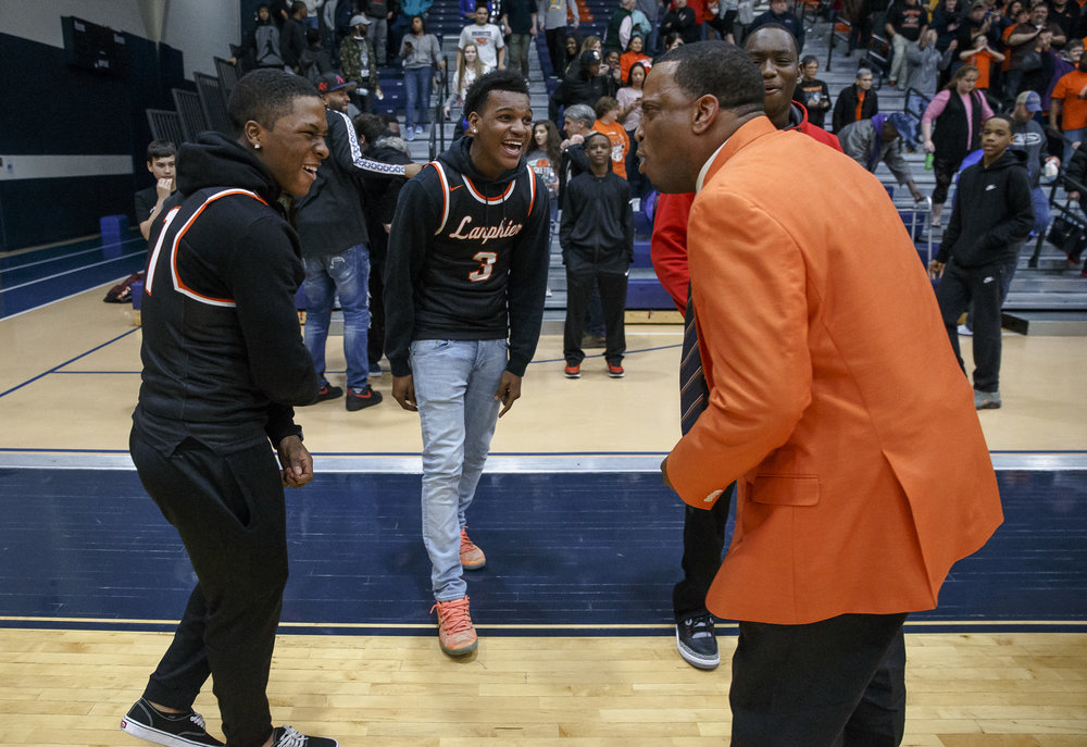 Lanphier graduates Yaakema Rose, left, Aundrae Williams, and Corrington Jones celebrate the Lions 33-19 victory over Lincoln with Lanphier boys basketball head coach Blake Turner after the Class 3A Rochester Regional title game at the Rochester Athletic Complex, Friday, March 2, 2018, in Rochester, Ill. [Justin L. Fowler/The State Journal-Register]