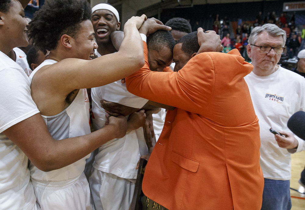 Lanphier's Cardell McGee (12) is swarmed by his teammates and head coach Blake Turner as the Lions celebrate their 33-19 victory over Lincoln in the Class 3A Rochester Regional title game at the Rochester Athletic Complex, Friday, March 2, 2018, in Rochester, Ill. [Justin L. Fowler/The State Journal-Register]