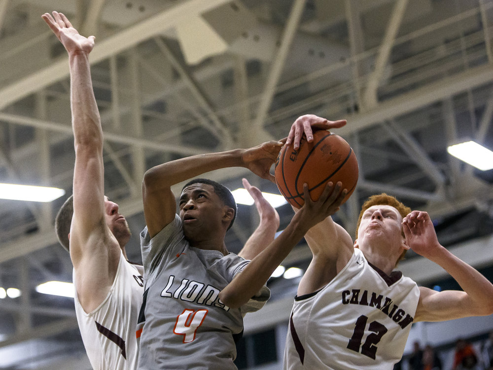 Lanphier's Larry Hemingway (4) has his shot blocked by Champaign Central's Sam Beesley (12) in the second half during the Class 3A Decatur Eisenhower Sectional semifinals at Eisenhower High School, Tuesday, March 6, 2018, in Decatur, Ill. [Justin L. Fowler/The State Journal-Register]