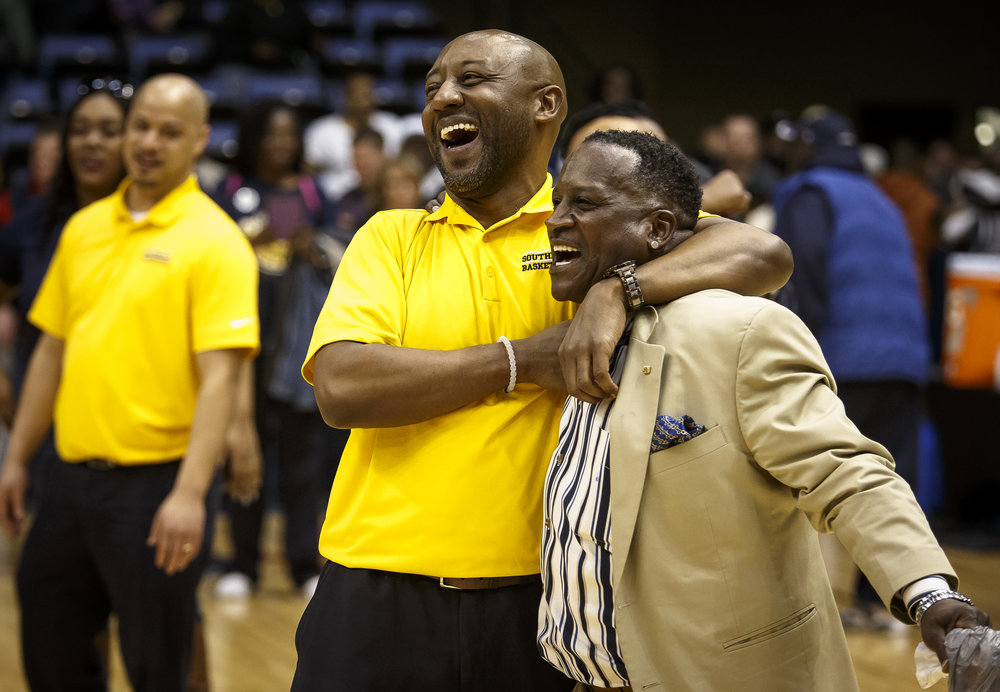 Southeast assistant coach Chuck Shanklin celebrates with Donnie Brandon, a member of the 1980 Spartans team, after Southeast defeated Marion 56-51 in the Class 3A Springfield Supersectional at the Bank of Springfield Center, Tuesday, March 13, 2018, in Springfield, Ill. [Justin L. Fowler/The State Journal-Register]