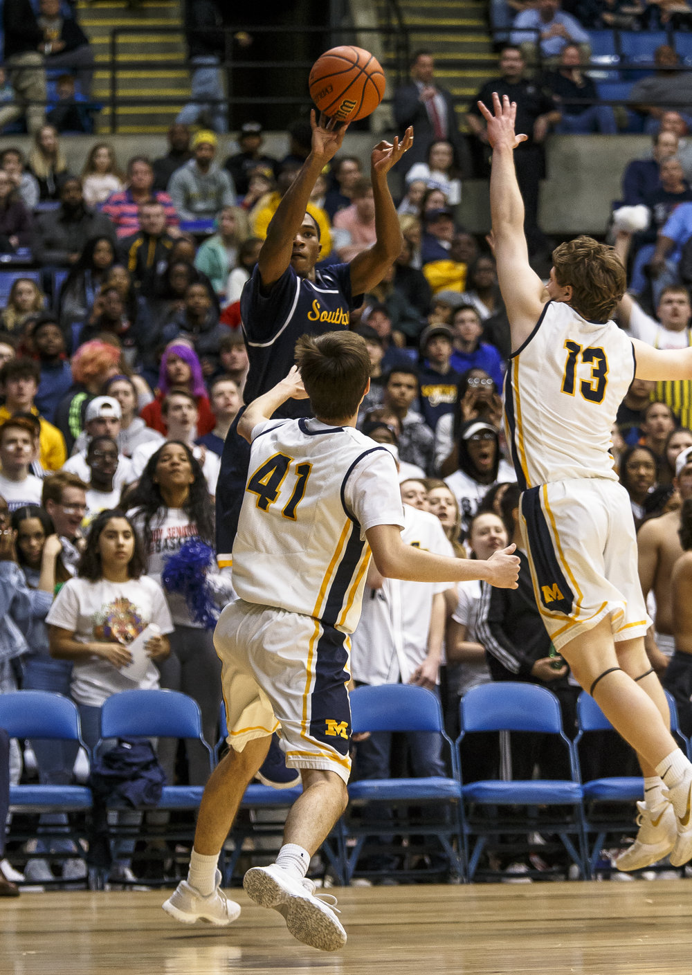 Southeast's Kobe Medley (11) shoes a 3-pointer against Marion's Cole Schafer (41) and Marion's Justin Saddoris (13) in the second half during the Class 3A Springfield Supersectional at the Bank of Springfield Center, Tuesday, March 13, 2018, in Springfield, Ill. [Justin L. Fowler/The State Journal-Register]