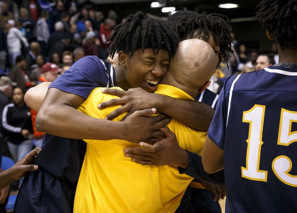 Southeast's Stepheon Sims (32) and Southeast's Terrion Murdix (4) celebrate with the Spartans after their 56-51 victory over Marion in the Class 3A Springfield Supersectional at the Bank of Springfield Center, Tuesday, March 13, 2018, in Springfield, Ill. [Justin L. Fowler/The State Journal-Register]