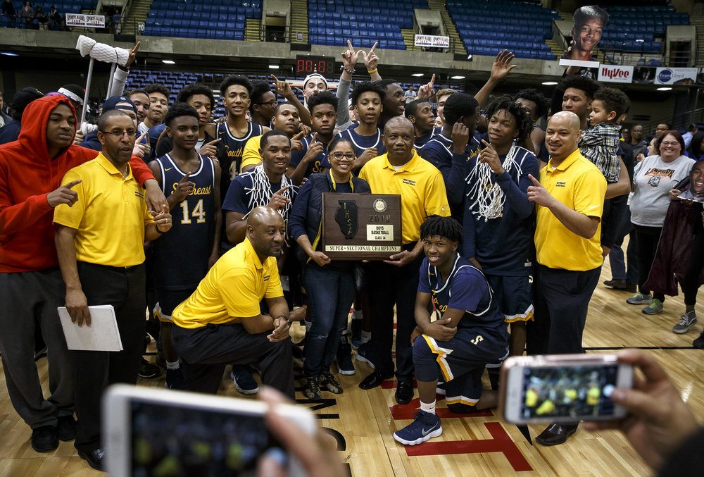 The Southeast Spartans join together for a photo as they celebrate defeating Marion 56-51 in the Class 3A Springfield Supersectional at the Bank of Springfield Center, Tuesday, March 13, 2018, in Springfield, Ill. [Justin L. Fowler/The State Journal-Register]