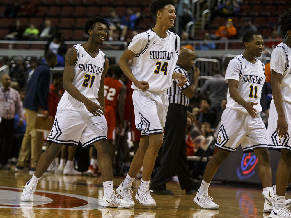 Southeast's Anthony Fairlee (21) and the Spartans celebrate after forcing North Chicago to call a timeout in the second half during the IHSA Class 3A State Tournament semifinals at Carver Arena, Friday, March 16, 2018, in Peoria, Ill. [Justin L. Fowler/The State Journal-Register]