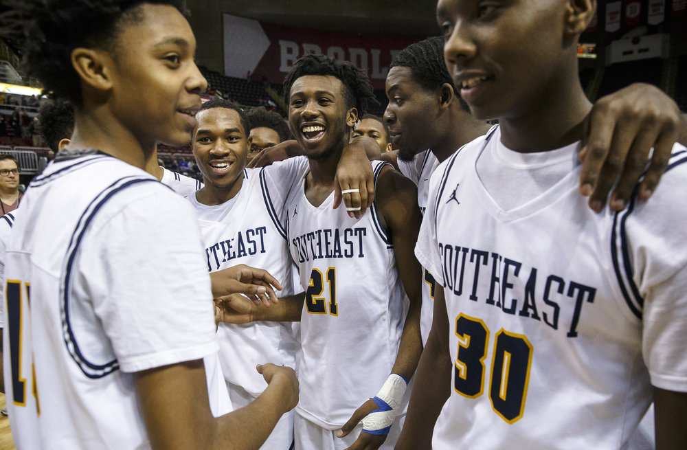 Southeast's Anthony Fairlee (21) celebrates with Spartans after they defeat North Chicago 60-38 in the IHSA Class 3A State Tournament semifinals at Carver Arena, Friday, March 16, 2018, in Peoria, Ill. [Justin L. Fowler/The State Journal-Register]