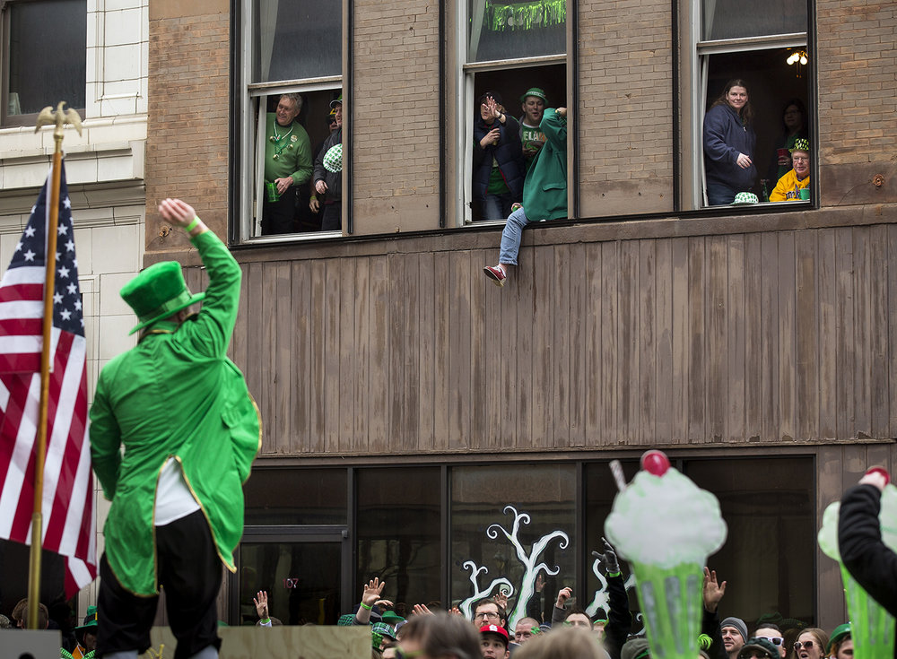 Dalton Doerfler, aboard the Shamrock 'n Roll Ryan's family float, tosses beads to revelers on Fifth Street during the St. Patrick's Day Parade Saturday, March 17, 2018 in Springfield, Ill. [Rich Saal/The State Journal-Register]