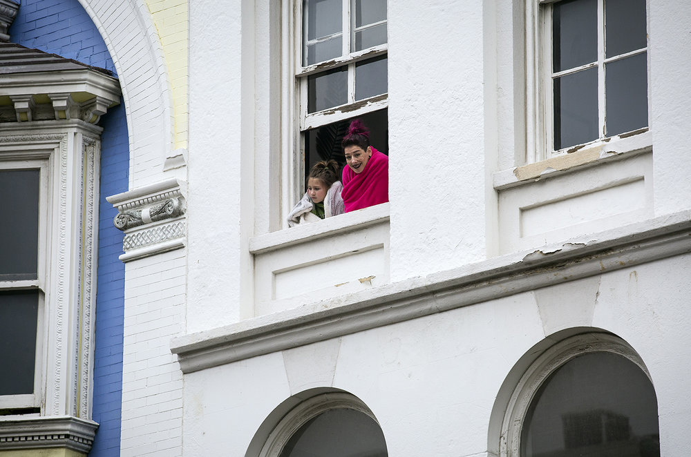 People watch the St. Patrick's Day Parade from a window above Fifth Street Saturday, March 17, 2018  in Springfield, Ill. [Rich Saal/The State Journal-Register]