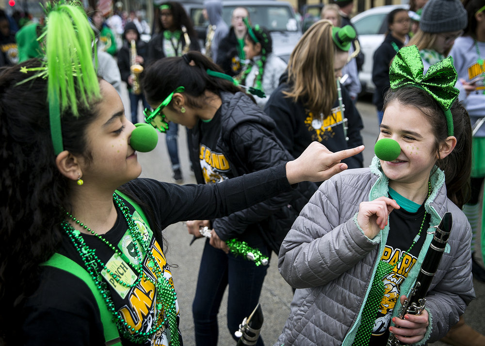 Nora Jasim, left, and Athia Schleyhan with the Lincoln Magnet School band, have fun with their green noses before the start of the St. Patrick's Day Parade Saturday, March 17, 2018  in Springfield, Ill. [Rich Saal/The State Journal-Register]