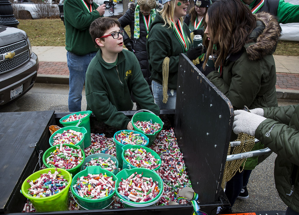 Jared Lauwerens begins to pass out buckets of candy to the others marching with a float from United Community Bank just before the start of the St. Patrick's Day Parade Saturday, March 17, 2018  in Springfield, Ill. [Rich Saal/The State Journal-Register]