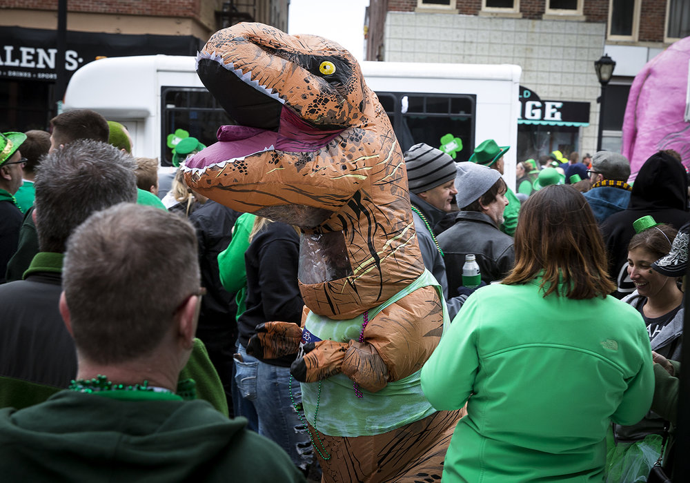A reveler wearing a Tyrannosaurus Rex costume walks through the crowd at the St. Patrick's Day Parade Saturday, March 17, 2018  in Springfield, Ill. [Rich Saal/The State Journal-Register]