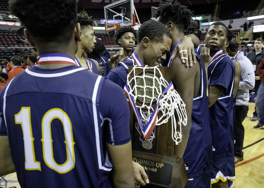 Southeast's Kobe Medley hugs Southeast's Anthony Fairlee after the Spartans picked up their runner-up trophy after losing to Morgan Park  during the 3A championship game at Carver Arena in Peoria, Ill., Saturday, March 17, 2018. [Ted Schurter/The State Journal-Register]