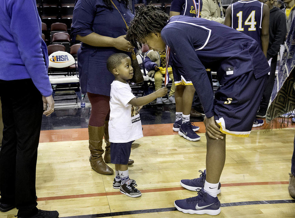 Three-year-old Eddie Snow looks up at Southeast's Terrion Murdix as he inspects his runner-up medal after the Spartans lost to Morgan Park  during the 3A championship game at Carver Arena in Peoria, Ill., Saturday, March 17, 2018. [Ted Schurter/The State Journal-Register]