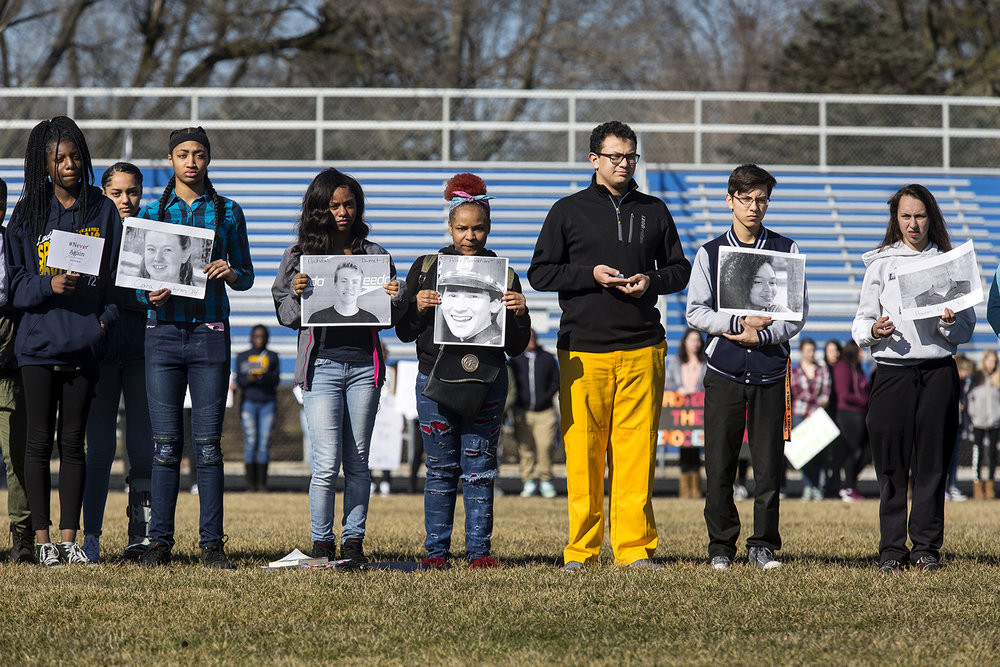 Southeast High School students hold photographs of victims of the mass shooting at Marjory Stoneman Douglas High School in Parkland, Florida one month ago, during a walkout at Southeast Wednesday, March 14, 2018 in Springfield, Ill. Southeast students and teachers participated in the national demonstration to raise awareness about gun violence in schools. [Rich Saal/The State Journal-Register]