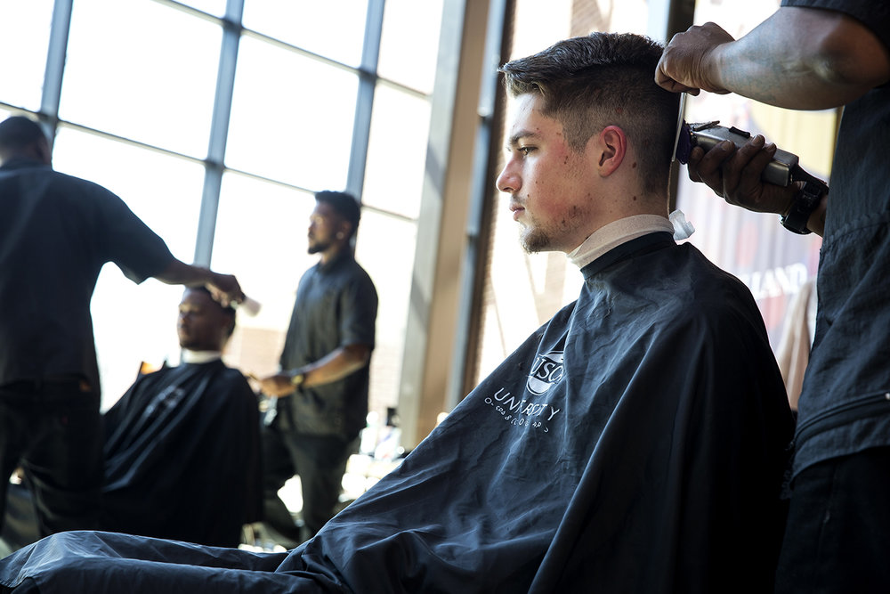 Burak Tokgoz, a Lincoln Land Community College student, sits for a haircut by Joseph Oso Commer Wednesday, March 21, 2018 in the commons at LLCC. Commer is one of five students in the barber program at the University of Spa and Cosmetology Arts in Springfield who spent a couple hours providing free haircuts to LLCC students and staff, something they do monthly as part of their training according to Breanna Washington, barber instructor at the university. [Rich Saal/The State Journal-Register]