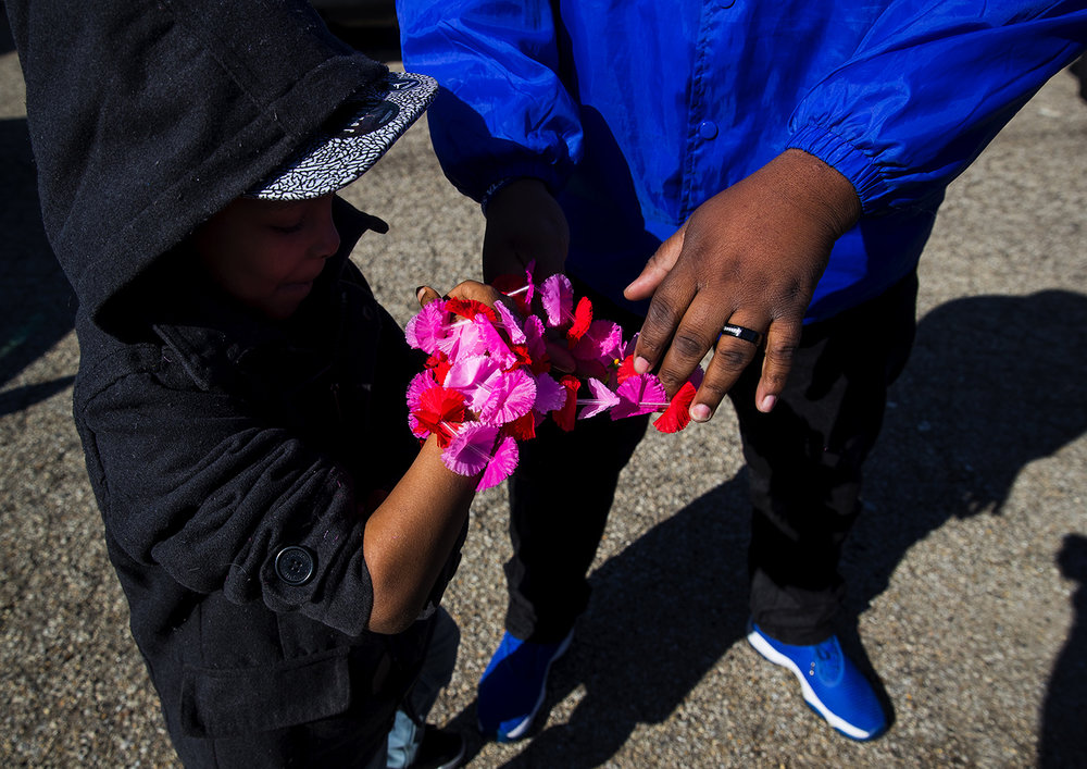 Johnny Johnson Sr. wraps a lei around his son Johnny Johnson Jr.'s wrist as they prepare to participate in the reenactment of the historic 1965 Selma to Montgomery March on Sunday, March 25, 2018. The lei's were also worn in the 1965 march. [Ted Schurter/The State Journal-Register]
