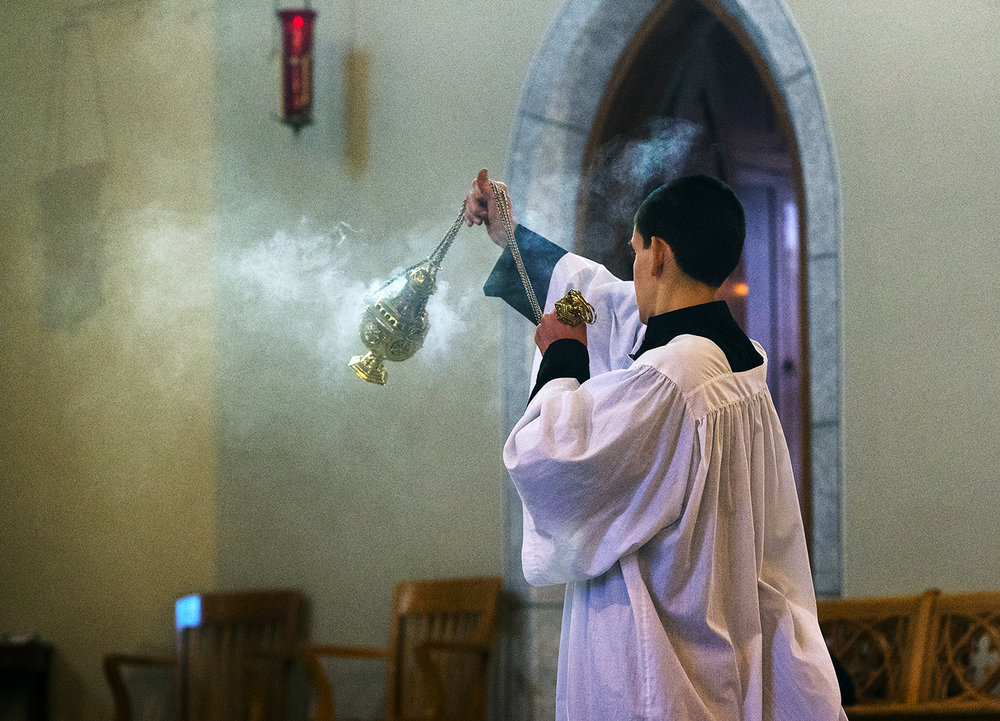 Incense wafts upward as an altar boy raises a thurible during the Latin Mass on Easter Sunday at Sacred Heart Church in Springfield, Ill., April 1, 2018. [Ted Schurter/The State Journal-Register]
