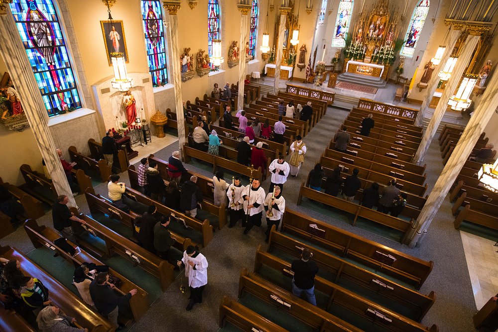 The cross is carried out of the sanctuary during the recessional at the Latin Mass on Easter Sunday at Sacred Heart Church in Springfield, Ill., April 1, 2018. [Ted Schurter/The State Journal-Register]