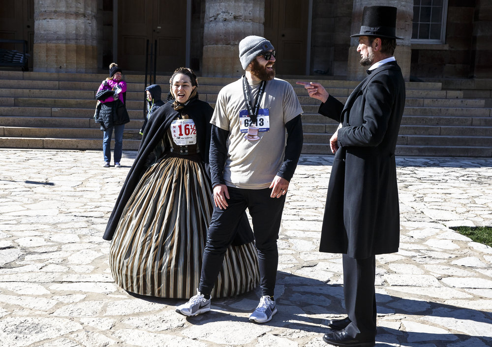 Nicholas Cordell, center, gets his photo taken with Michael Krebs and Debra Ann Miller, portraying Abraham Lincoln and Mary Todd Lincoln, after finishing the 2018 Lincoln Presidential Half Marathon, Saturday, April 7, 2018, in Springfield, Ill. [Justin L. Fowler/The State Journal-Register]