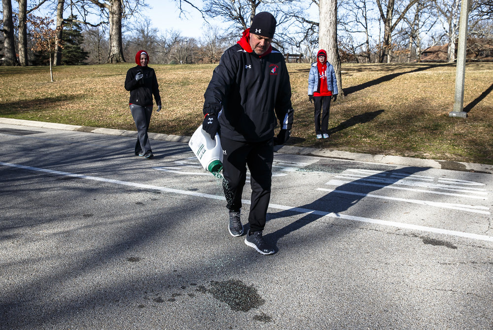Pleasant Plains girls track coach Rob Havens puts down ice melt around the water station, run by the Pleasant Plains Girls Track team, as water spilled from the runners turned to ice with temperatures in the 20s during the 2018 Lincoln Presidential Half Marathon, Saturday, April 7, 2018, in Springfield, Ill. [Justin L. Fowler/The State Journal-Register]