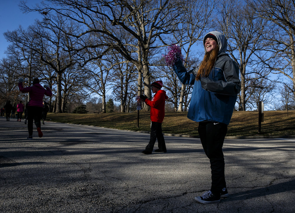 Emily Higginson, 17, right, and Emily Russel, 18, center, encourage the runners as they turn in to Washington Park off of Williams Boulevard next to a water station run by the Pleasant Plains Girls Track Team during the 2018 Lincoln Presidential Half Marathon, Saturday, April 7, 2018, in Springfield, Ill. [Justin L. Fowler/The State Journal-Register]