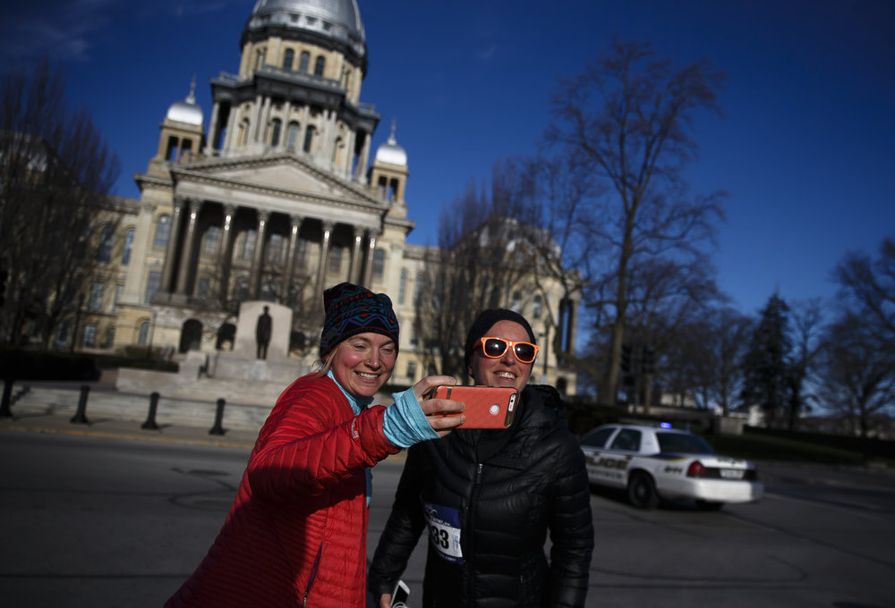 A pair of runners stop for a selfie in front of the Illinois State Capitol during the 2018 Lincoln Presidential Half Marathon, Saturday, April 7, 2018, in Springfield, Ill. [Justin L. Fowler/The State Journal-Register]