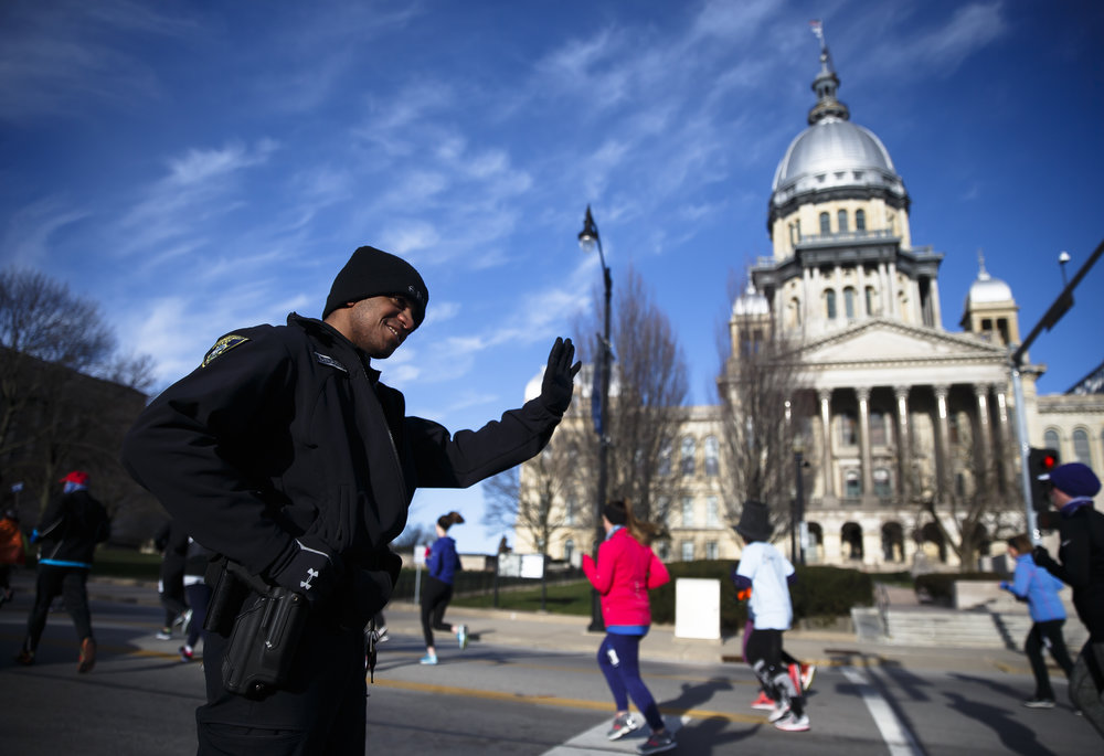 Springfield Officer Derek Wilkerson greets runners as they they make the turn south on Second Street on their way towards Washington Park during the 2018 Lincoln Presidential Half Marathon, Saturday, April 7, 2018, in Springfield, Ill. [Justin L. Fowler/The State Journal-Register]